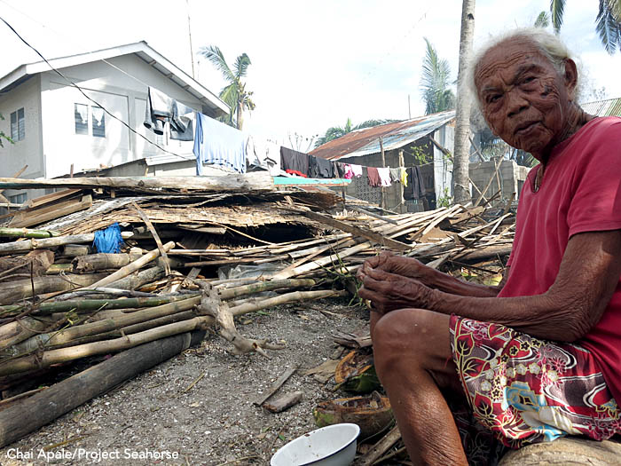 A woman sits in front of the ruins of a house in Bantayan Town. Photo: Chai Apale/Project Seahorse
