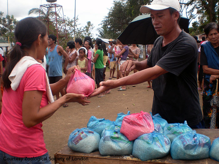 Field staff hand out relief packs to villagers. The packs contain food, clean water, soap, and essential medicines. Panay, Philippines.  Photo courtesy of ZSL