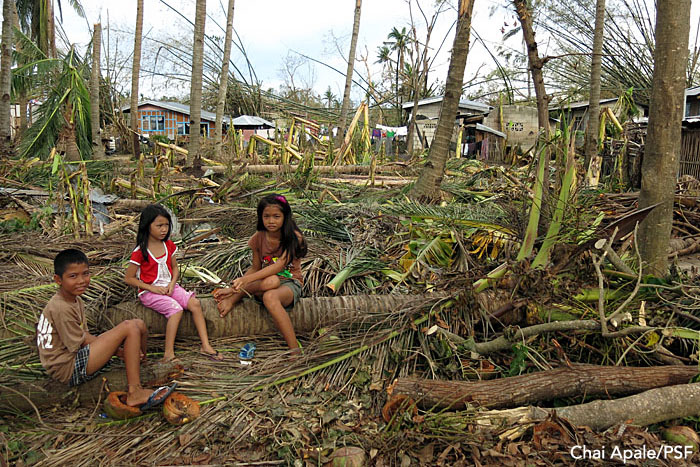 Kids rest on a knocked-down tree outside their village. Bantayan, Philippines.  Photo: Chai Apale/PSF