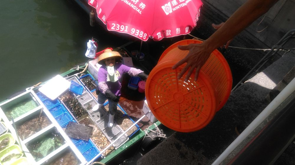 This is Sai Kung, a fishing/recreational port in Hong Kong, where trading seafood is done slightly differently - people standing on the pier stick out a net or a basket to the fishers on the boat and exchange seafood & money.  TC Kuo/Project Seahorse