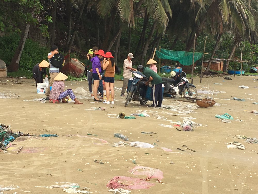 Fishers and buyers selling their daily catch on a beach, littered with plastic, in Mui Ne, Binh Thuan Province. A popular weekend getaway from Ho Chi Minh City, local and foreign tourists visit the beaches to buy seahorses and other seafood.