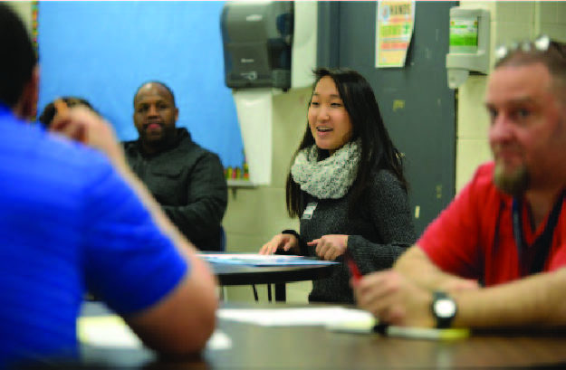 Jenny kwon, an undergraduate researcher working with working for kids: building skills, discusses lesson plans with instructors at the shuman juvenile Detention facility in Pittsburgh's east end.