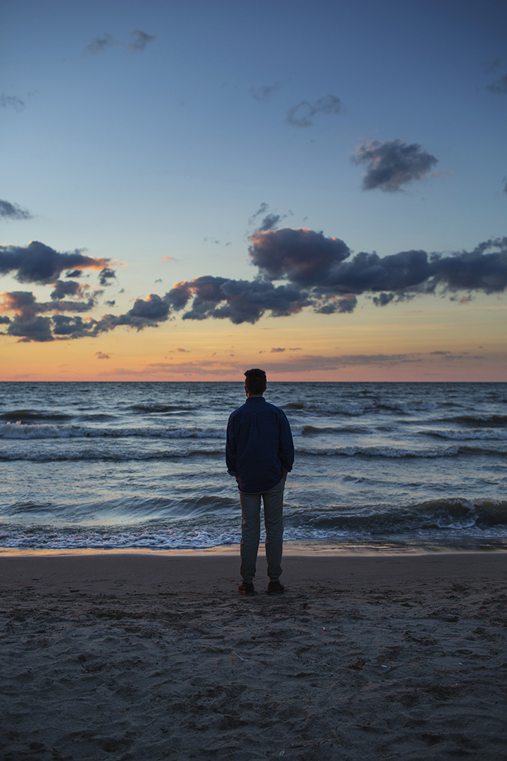 Man gazing at Lake Erie at duskin Cleveland, Ohio. Photo by Dustin Franz