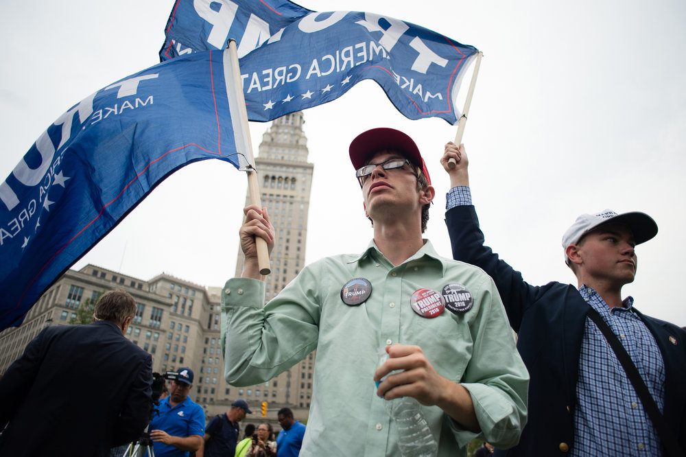 David, left, and Christian (last names witheld) wave Donald Trump flags in Public Square during a demonstration Thursday in Cleveland. (Dustin Franz for ESPN)