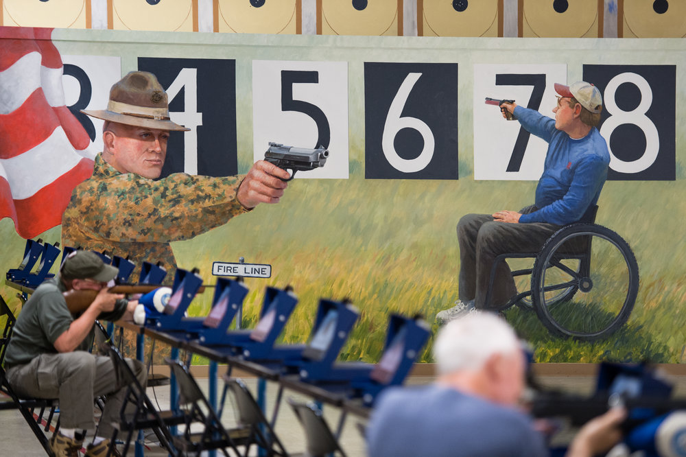 A mural depicting a service member and a civilian shooting targets at the air rifle range at Camp Perry.