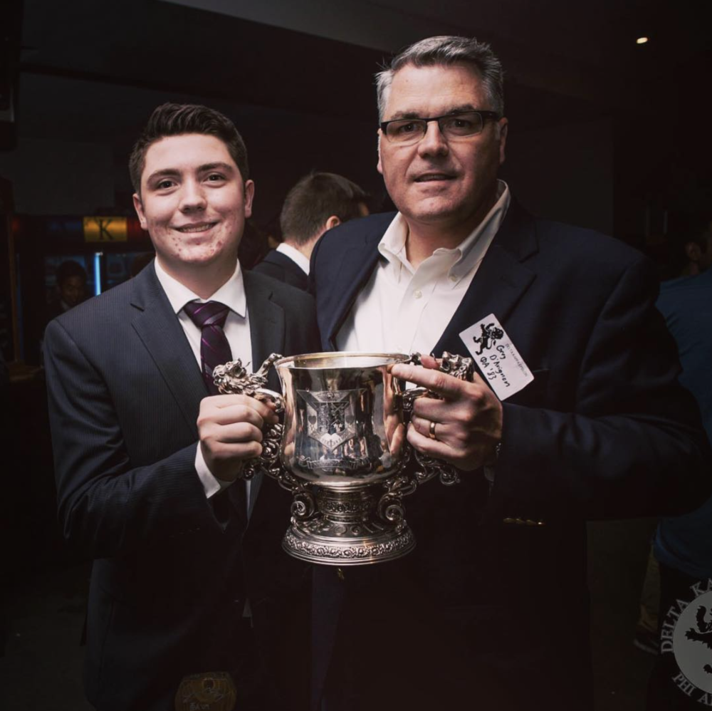 Father and son Matt D'Avignon (PA '14) and Gerry D'Avignon (PA '83) show off The Lion Trophy, awarded annually to the best ∆KE Chapter.