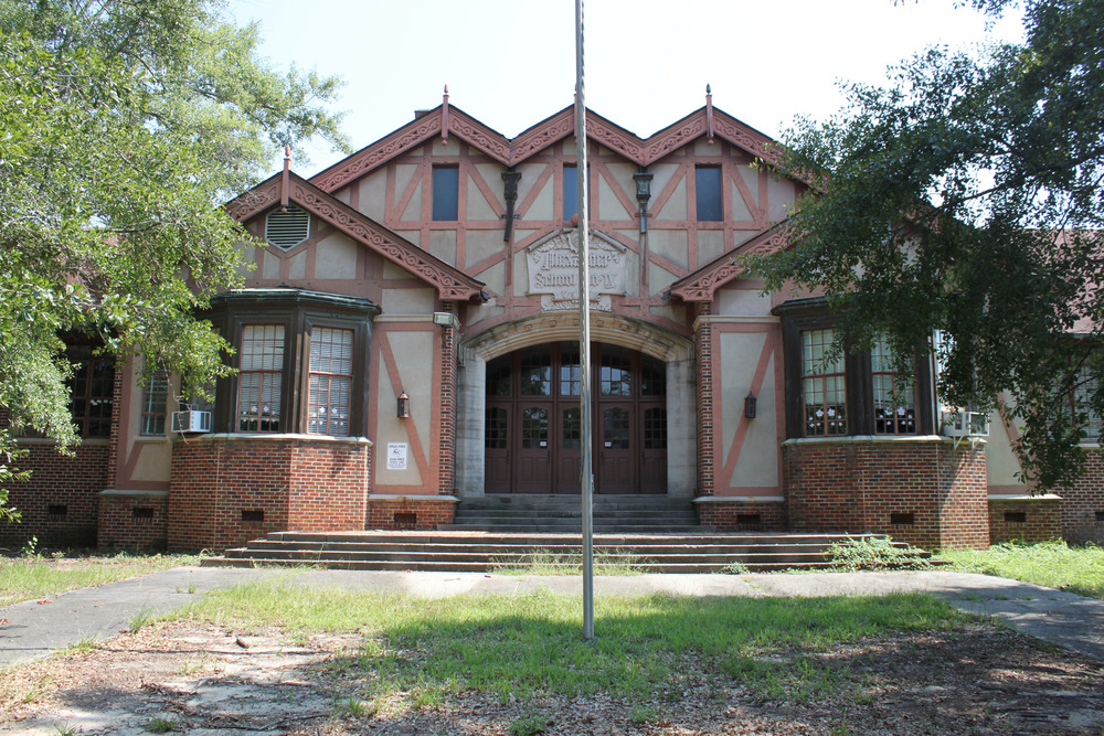 "Alexander IV Elementary School was established in 1932 as the fourth free school supported by the Elam Alexander Trust. Mr. Elam Alexander, a notable architect, believed that free, quality education was paramount for the success of individuals, which in turn would lead to the success of Macon as a community. During his lifetime, Mr. Alexander gave generously to many educational institutions, and in his will, he set up the Alexander Free School Board, later known as the Elam Alexander Trust. This organization continues to promote education in Macon-Bibb County.  This particular elementary school was built in the Ingleside neighborhood to relieve overcrowding at the Bellevue and Clisby Schools. The Ridge Avenue location was more convenient for many of its new students, who lived in the recently established Ingleside neighborhood. The community waited in great anticipation for its new school, which the  Macon Telegraph  described as a ""gabled, bronze-hued, English type"" building. Such was the anticipation that the newspaper even wrote a description of the interior: ""the mellow cream and brown interior of the school with its bronze trimmings and rose-tiled floors.""  The excitement continued after Alexander IV's opening. Ms. Nell Collins, who both taught the seventh grade and served as the first principal, asked the Parent Teacher Association to hold a special tea, which formally unveiled the school in November 1932. Just a month earlier, a plaque was dedicated to Elam Alexander at the front entrance of the school. That plaque is still in place today.  Alexander IV's prominent role in the community continued in many ways through the twentieth century. For instance, the school fielded a dominant football team for Macon's annual Pony Bowl, a football game played around Thanksgiving, from 1949 to 1960. The school's integral role in the community came to a close in June 2011, when Alexander IV closed its doors to students.  Today, the building's steeply pitched gables, exposed beams, and intricate ornamentation stand empty to students. The Bibb County Board of Education declared the building surplus in 2013 and is seeking a new use for the significant building, which is a contributing building in the proposed Ingleside National Register District.  Historic Macon Foundation looks forward to working with the neighbors and the Board of Education to find a new use for the iconic school building. Across the country school buildings have been adapted to multiple uses, and we are confident Alexander IV will once again be an anchor and asset for the community.    UPDATE:  The Bibb County Board of Education approved the sale of Alex IV to the Macon-Bibb Country Land Bank Authority. The Land Bank Authority will hold the building as Historic Macon works with a committee to send out a request for proposal to developers.     Dover Development has been selected to renovated Alex IV into a senior living facility.  Read more."