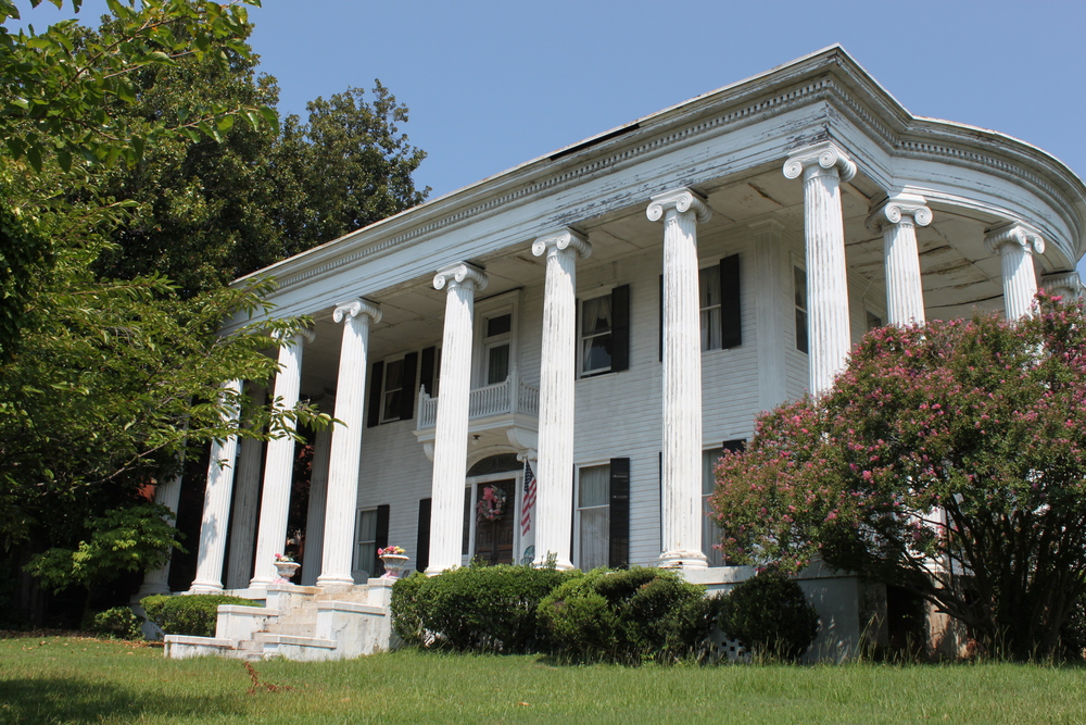 "UPDATE: A family has purchased the Boonybrae-Bedgood House and will rehabilitate it as a single-family home, its original use. Rehabilitation is well-underway.  Known by many family names, the Greek Revival house at 1073 Georgia Avenue was built between 1838 and 1839 by James Goddard of Athol, Massachusetts. Goddard sold the house only a couple years later to another Massachusetts native, George Newhall. In 1846, Isaac Scott, president of the Macon and Western Railroad as well as the Upson County Railroad, purchased the house. Railroads were a very important part of Macon's industrial success in the nineteenth century, and Scott played a prominent role in that business during the time he lived in this architectural masterpiece.  In 1865, Walter Arnold Huff bought the house after the Scotts moved to New York. Continuing the house's tradition of prominent residents, Huff was Mayor of Macon from 1870 to 1880. Then in 1875, Thomas Greshman owned and lived in the house. Although Thomas B. Greshman did not serve in political office himself, John Jones Gresham, his father, served as Mayor of Macon in the 1840s and as a State Senator and Representative.  Thomas Gresham moved to Baltimore in 1886, and the house went through a number of different hands until 1893, when William McEwen Johnston purchased the house for his wife, Flewellen Reese. She renamed with the house ""Bonnybrae,"" which it was commonly known as at least until the 1970s. During this era, the house underwent a dramatic change after notable architect, Neil Reid, nearly doubled the house and transformed it to the house we see today.  In 1913, the house was converted into apartments units, and even hosted the ""Hinkle Clinic"" in the 1920s. The structure went through a variety of uses over the next fifty years, until the United Methodist Church purchased it in 1970. In 1976, the Bedgood family purchased the home, and the daughters still own it today.  This high-style structure retains its magnificent white columns on the façade that wrap around to a secondary elevation. The spacious lawn to the side of the house, which faces the rear of Mercer University's Walter F. George School of Law, grants views of both the original house and a larger addition on the rear. Both bays still showcase elaborate dentil work under the eaves.  Today, the Bonnybrae-Bedgood House is one of Macon's last antebellum houses without an owner. Historic Macon Foundation looks forward to working with the current owners to help market and promote the house to a new buyer for the next chapter of the house.    UPDATE:    A family living in north Macon purchased the Bonnybrae-Bedgood House and will rehabilitate it as a single-family home. Work is underway and the family is taking advantage of Historic Macon's    tax credit consulting service    to complete renovations."