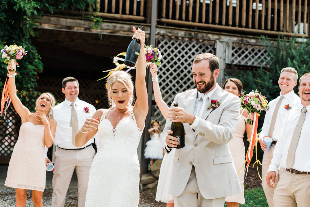 popping champagne at Armstrong Farms Wedding Venue