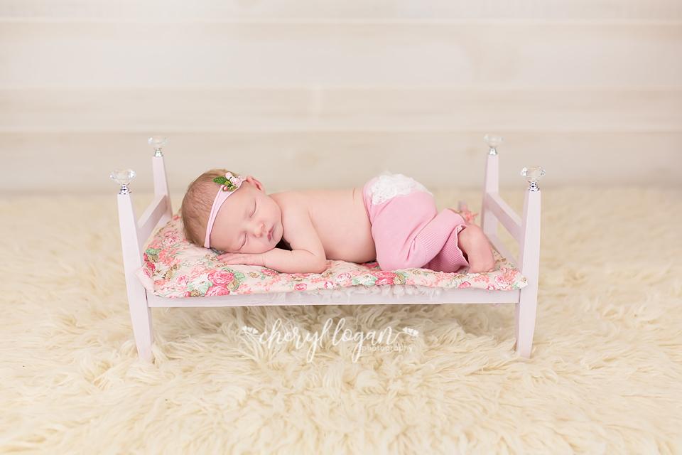 Newborn girl on bed.