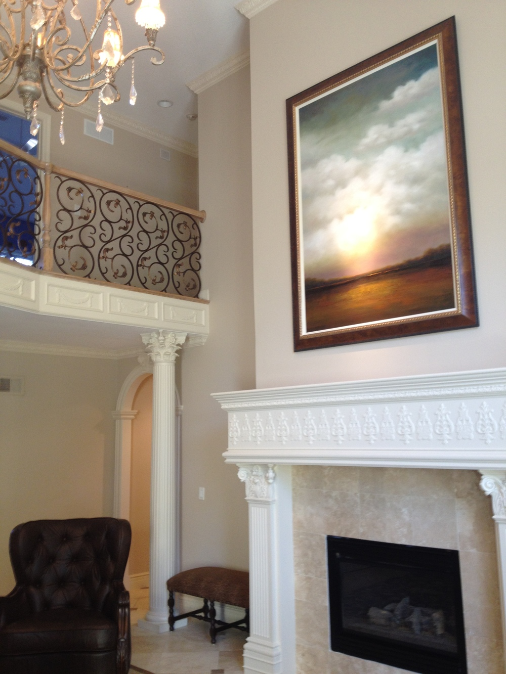 The large scale and soaring skies of this painting connects the first and second floor of this home.