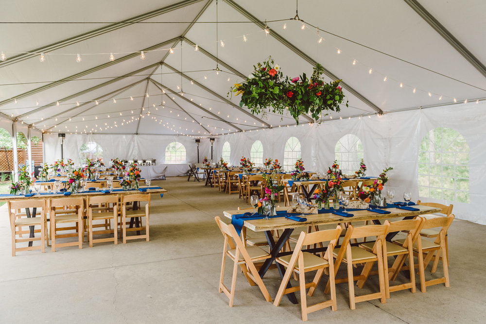 Farm tables and hanging floral chandelier in tent