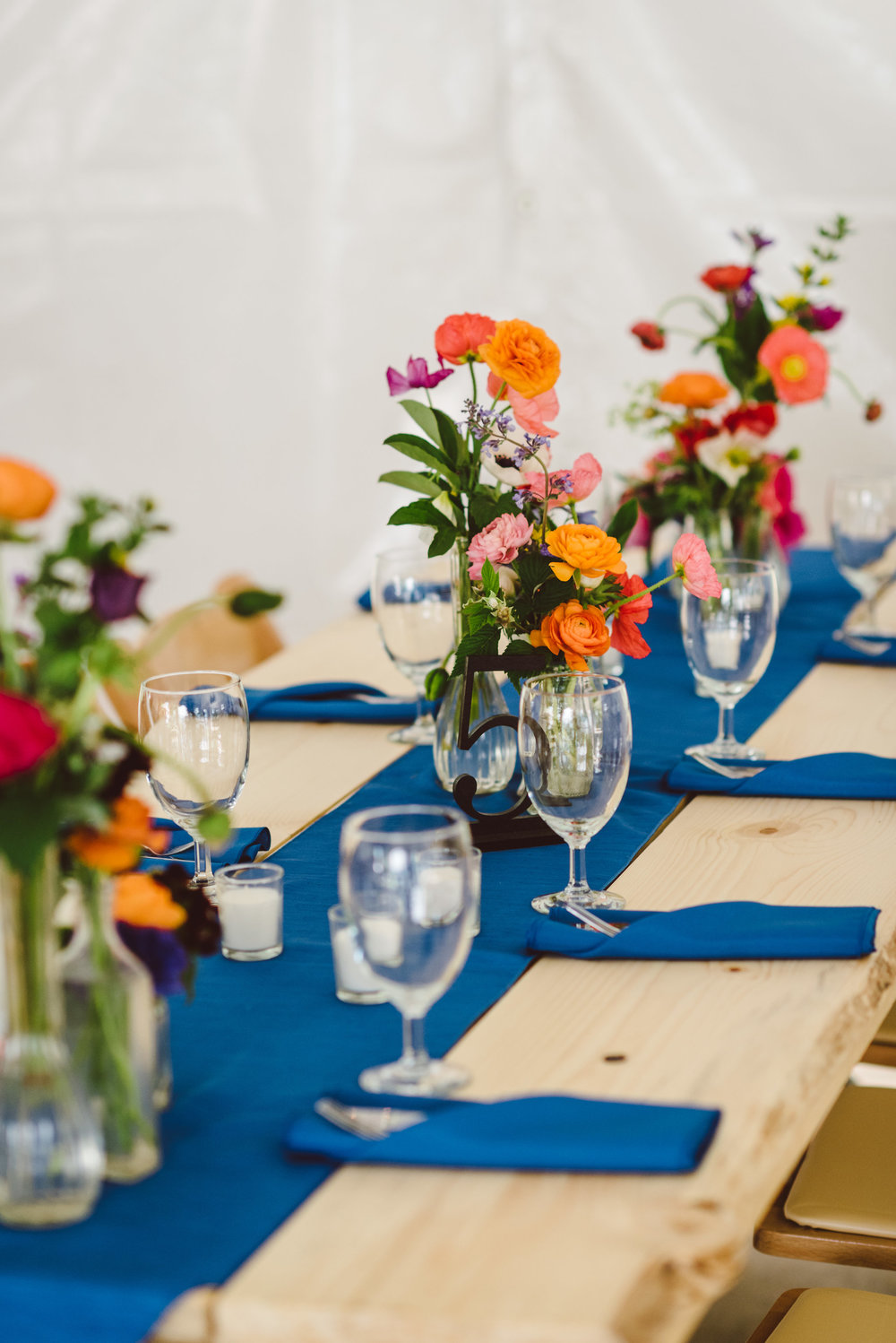 Farm tables with bright flowers and blue accents