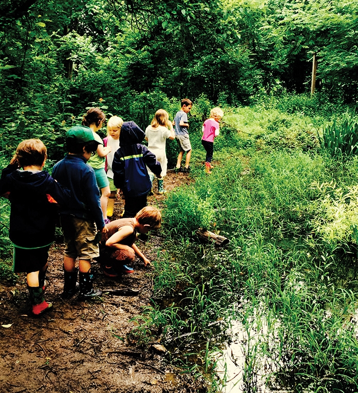 Elementary students at the Schuylkill Center for Environmental Education get down in the mud during a hike | photo by Rebecca Dhondt