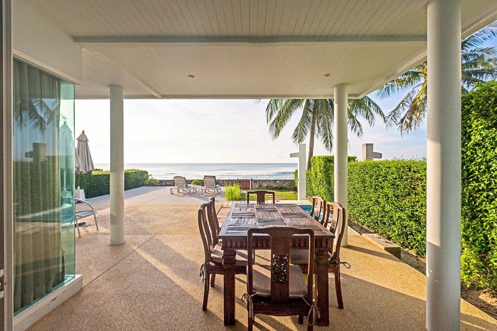 Matbordet påuteplatsen med utsit mot strand och hav.