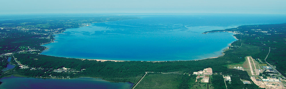 Web photo of Little Traverse Bay.  Harbor Springs is tucked in behind the peninsula upper right; Petoskey is upper middle left. The beach is middle bottom.  And yes, the water really is this color. From Tip of the Mitt Watershed Council website (https://www.watershedcouncil.org/)