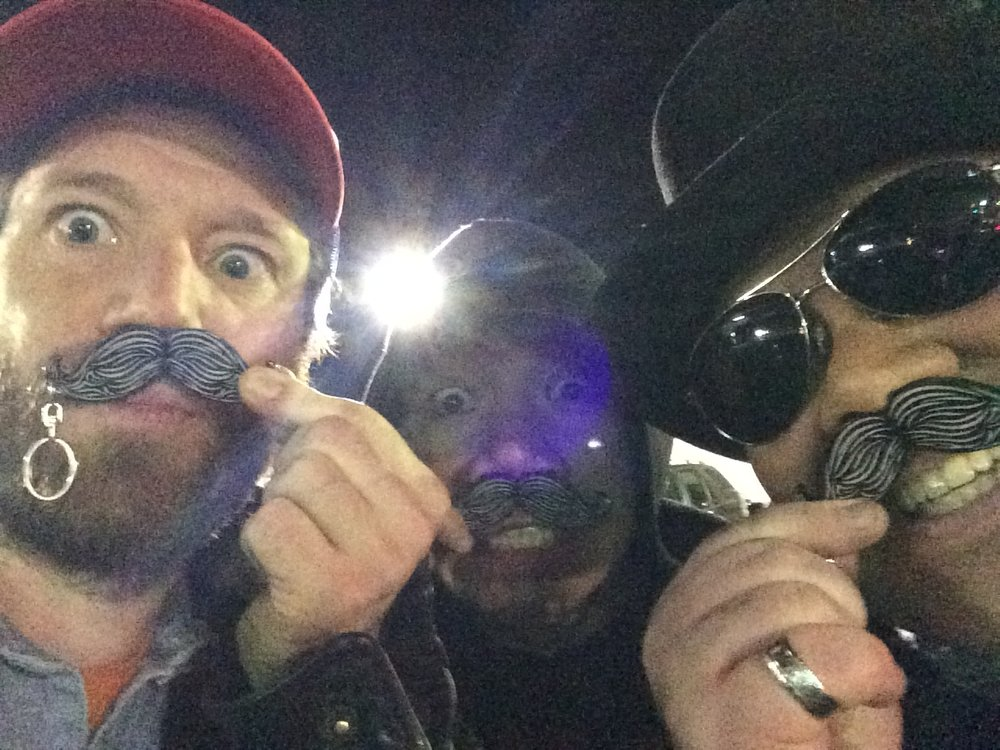 Graeme Hinde, Eric Volfange, & Manny Decoria pose with fake mustaches after performing for acorporate event at Bardot in Hollywood.