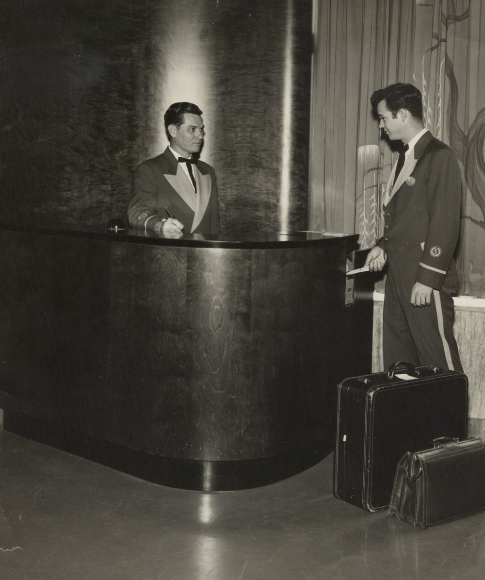 Registration desk in the lobby of The Shamrock Hotel. Bell-hop Johnny Sicola is pictured here in his hotel uniform. Circa 1955.  The Heritage Society Permanent Collection
