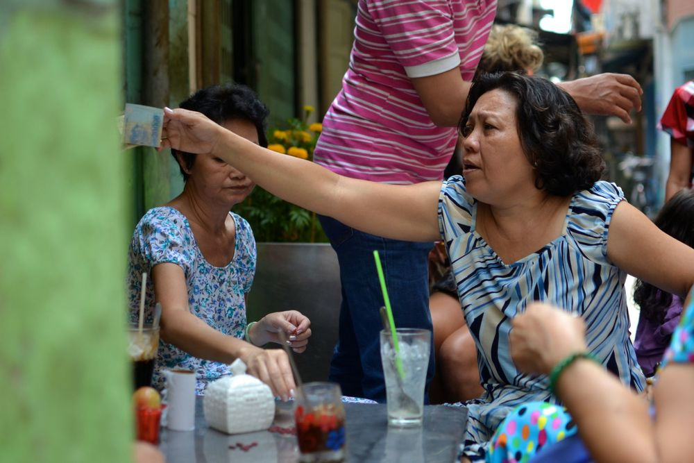 Women drink morning coffee and socialize near their homes in an alley in Ho Chi Minh City