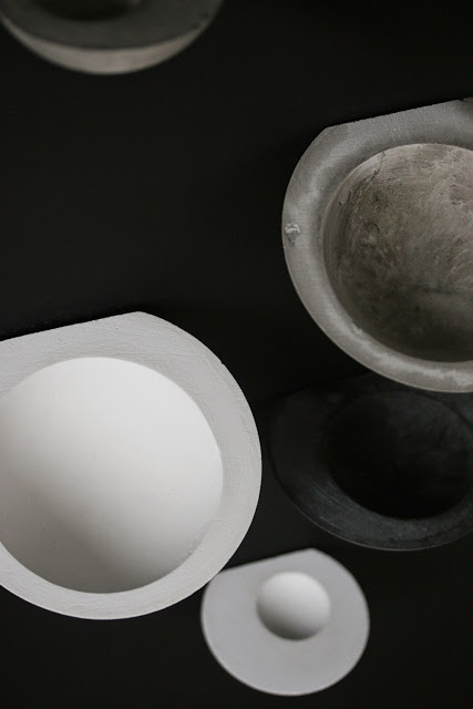 A close view showing gray, black, and white wall bowls with beautiful texture and asymmetry
