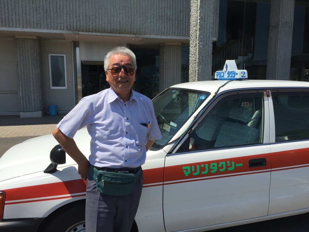 Masao Tachibana utilizes his job to promote tourism and bring attention to Yamada's past suffering in the 2011 earthquake and tsunami.