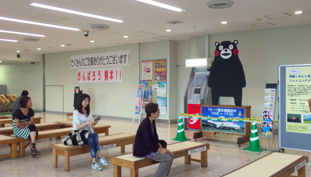"The waiting area inside Kumamoto Airport. Kumamoto's famous mascot Kumamon stands next to posters with words of encouragement like ""Ganbare (You can do it) Kumamoto!"""