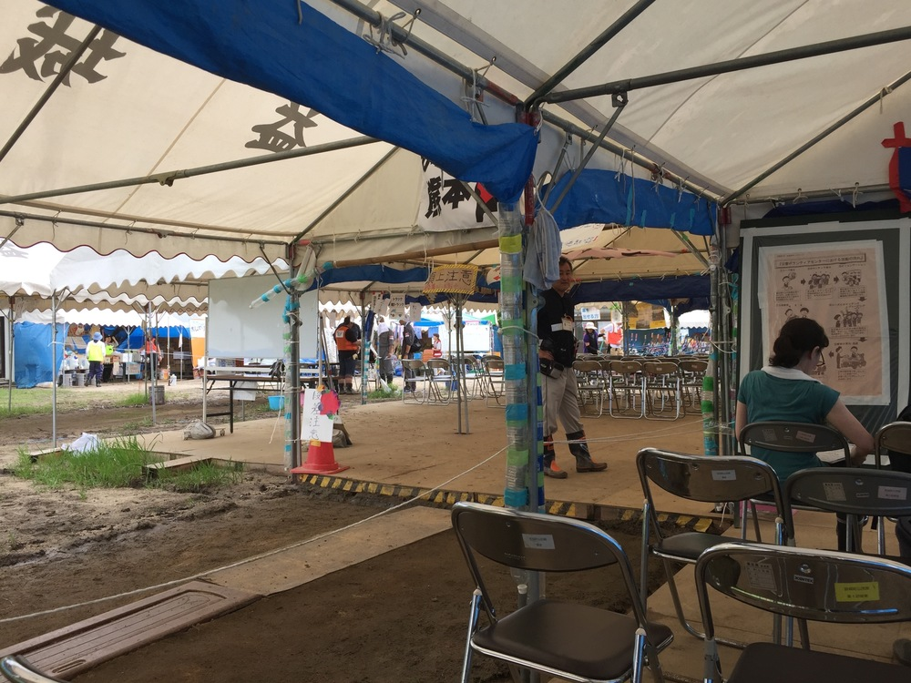 The volunteer center is made with multiple tents and a mud floor