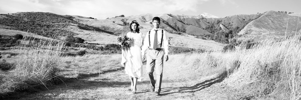 Bride and Groom Walking Hand-in-Hand with Flowers by Kate Healey