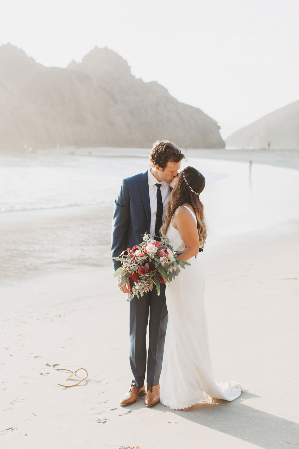 Couple Kissing on the Pfeiffer Beach with Large Bouquet by Big Sur Flowers