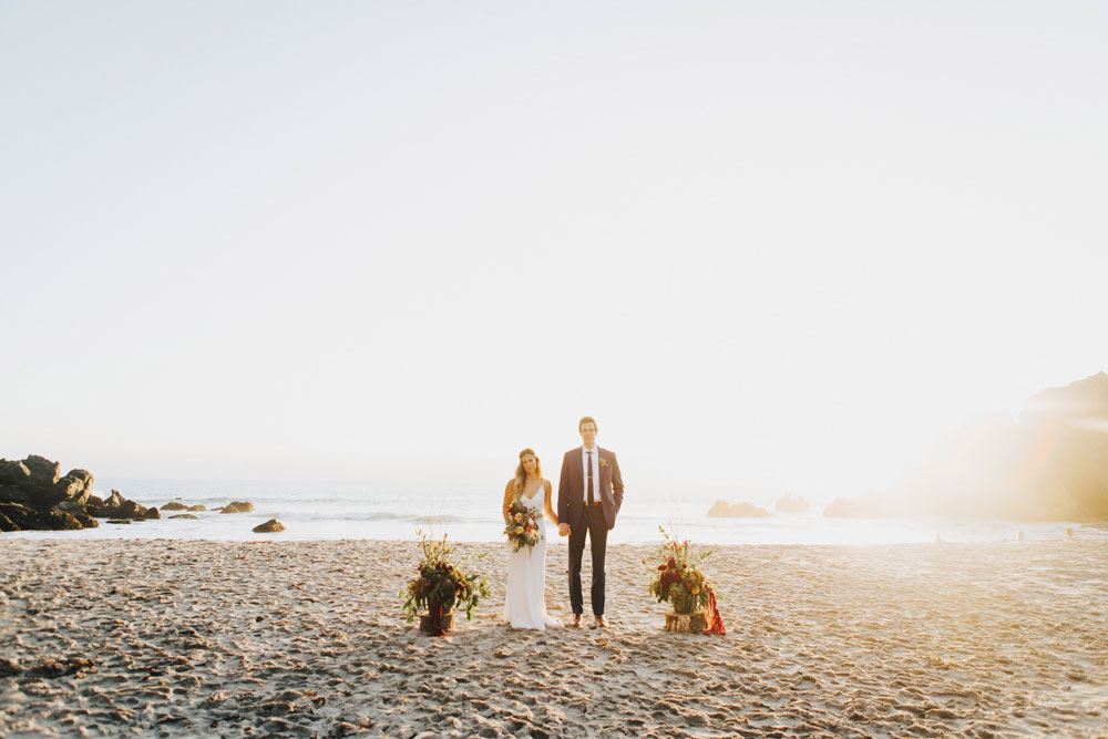 Bride and Groom on Big Sur Beach with Flowers by Kate Healey