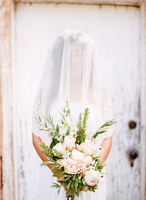 Beautiful Bride in a Veil Holding Her Bouquet