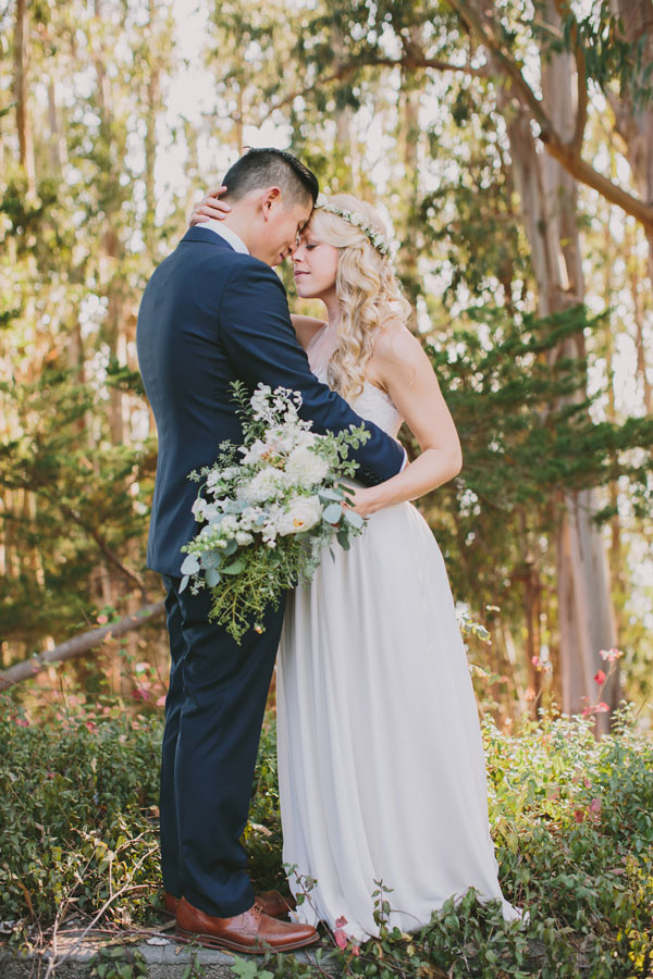Bride and Groom Embrace with a Fresh Bridal Bouquet by Big Sur Flowers