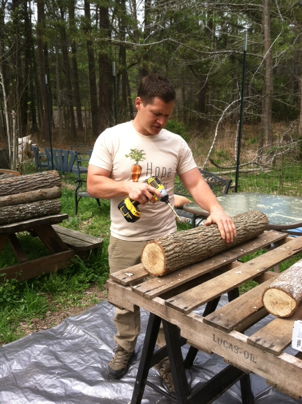 Jeremy demonstrates how to drill the holes for the                                  dowels into a log.