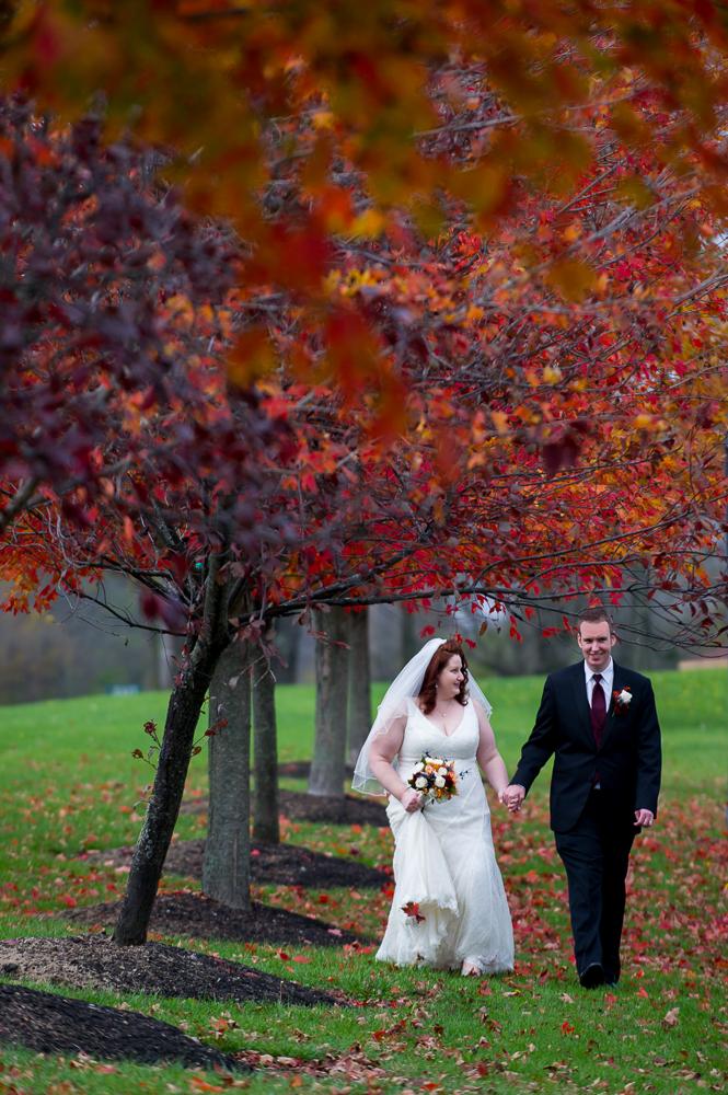 2-dayton-wedding-walking-bride-groom-holding-hands-fall-leaves-dominick-lofino-park.jpg