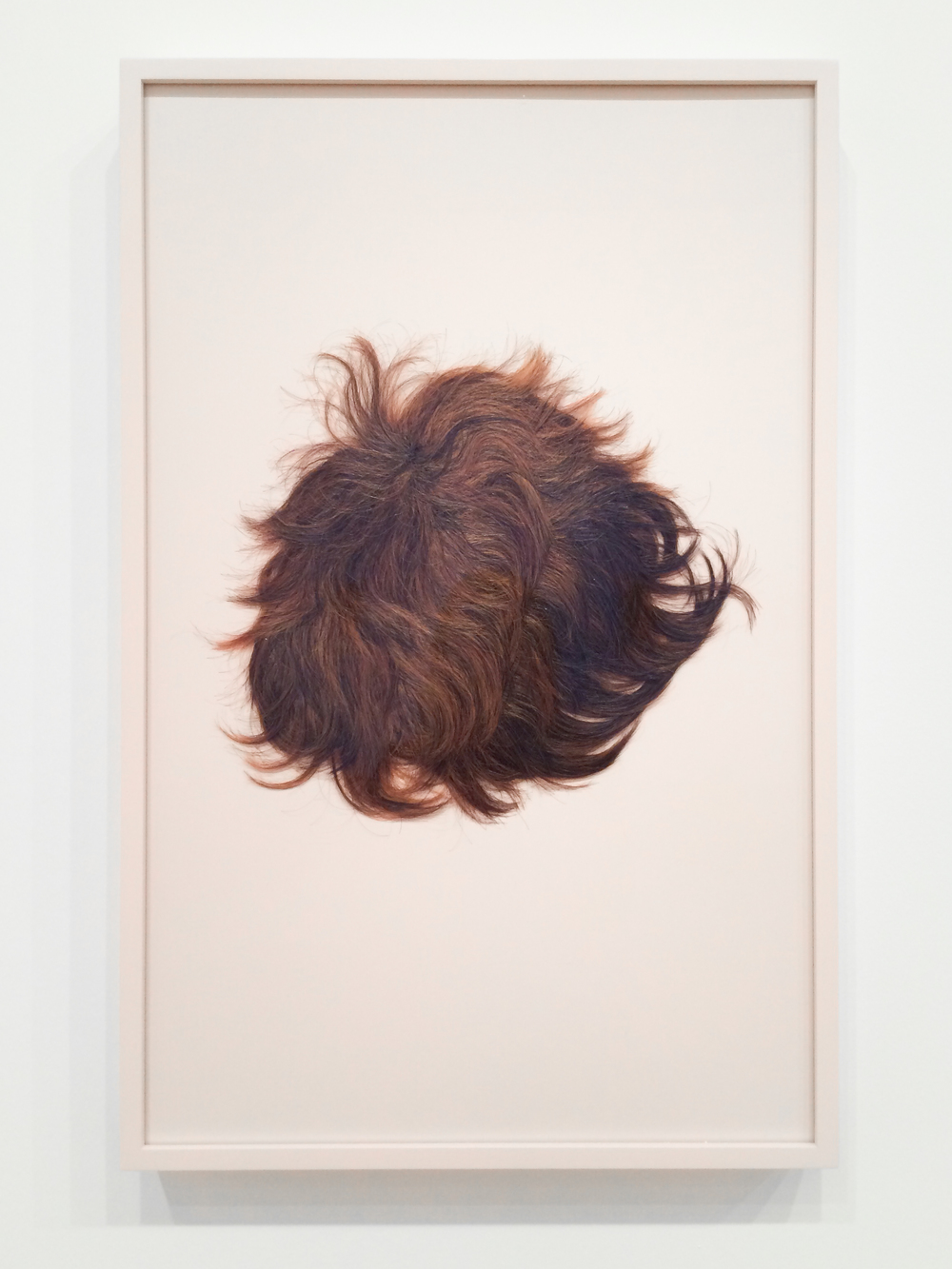 Nina Beier, Curtain Bang Crop, 2014. Human hair wig, painted frame, 42.2 x 65.10 x 5 cm. Courtesy de l'artiste et Metro Pictures, New York.