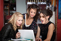 CR--Girls-looking-surprised-around-laptop