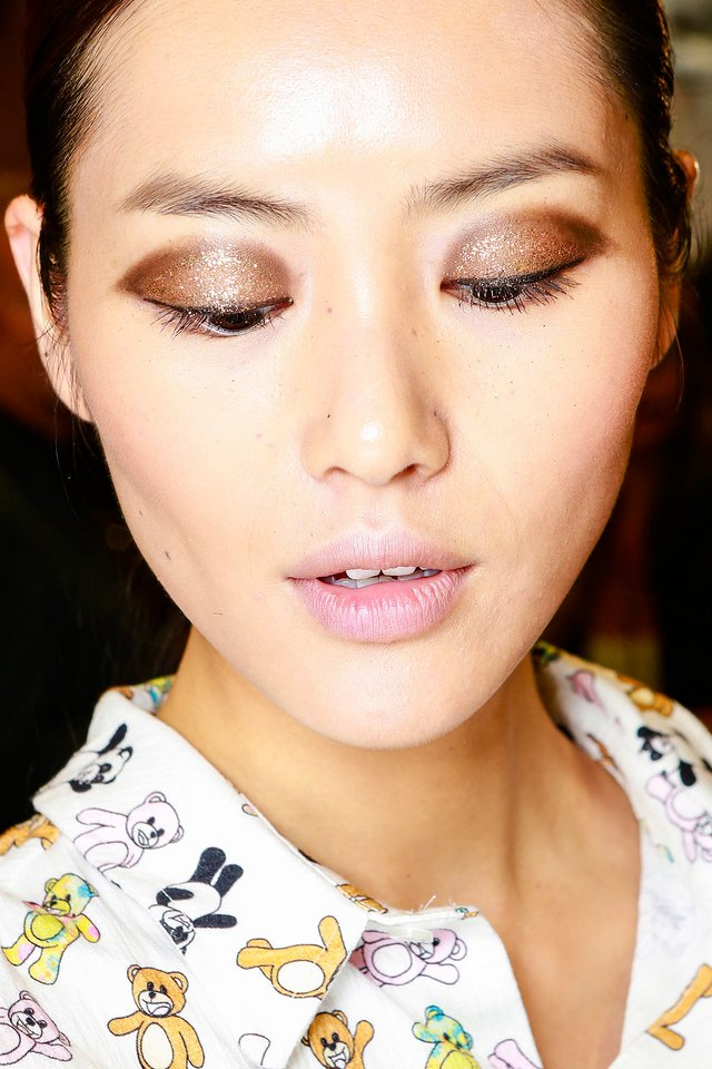 BRONZE BEAUT Take a metallic shadow up a notch by coating it with a thin layer of matching glitter like face painter Diane Kendal did at Jason Wu's Spring '14 show. Base eyes with a dewy foundation (like Lancôme Teint Visionnaire Skin Correcting Duo) to give the shimmery particles something to grip onto, then blend a brown liner pencil through the crease—leaving the middle of the lid bare. Using a damp brush, apply a fine rose gold glitter to the centre for a glam finish.