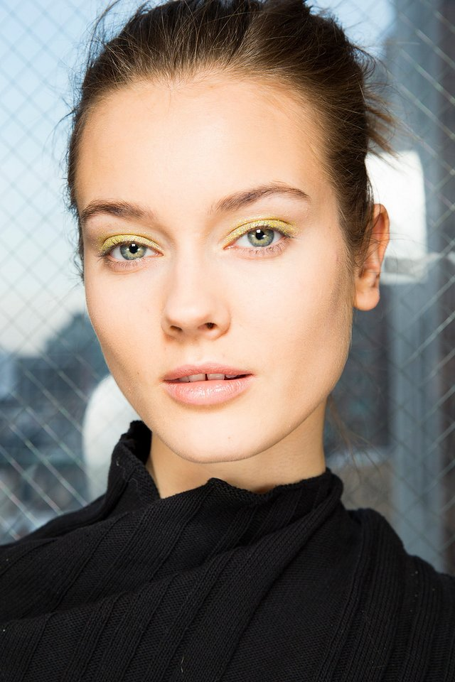 NEUTRAL TINGED WITH GREEN Give an uptown look (like the luxe cashmere and fur from Altuzarra's Fall '14 collection) a downtown vibe with glitter in an unexpected color. Tom Pecheux employed a green-gold hue, applying the particles to models' lash lines with a brush coated in Homeoplasmine, a moisturizing ointment. Diffuse the sparkles over the lid and up toward the brow bone with a dry, fluffy brush. Keep the rest of the face relatively bare, save for a flesh-coloured lipstick.