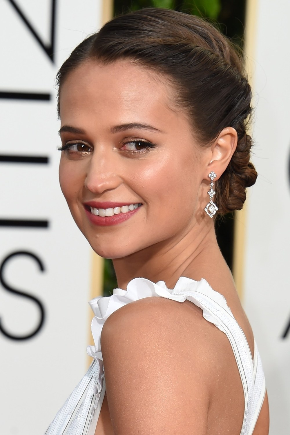 A twisted up-do showed off the detailing of Alicia Vikander's Louis Vuitton gown, whilst gold eyeshadow and pink lipstick made up her beauty look.