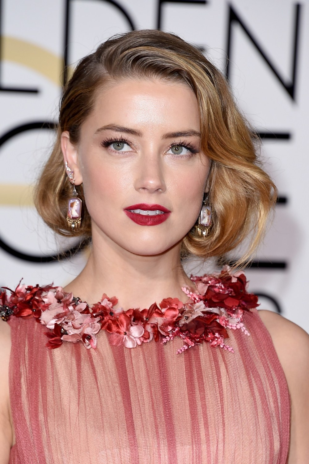 Amber Heard opted for Old Hollywood glamour, with curled hair worn in a faux bob, matt red lips and eyes defined with metallic shadow.
