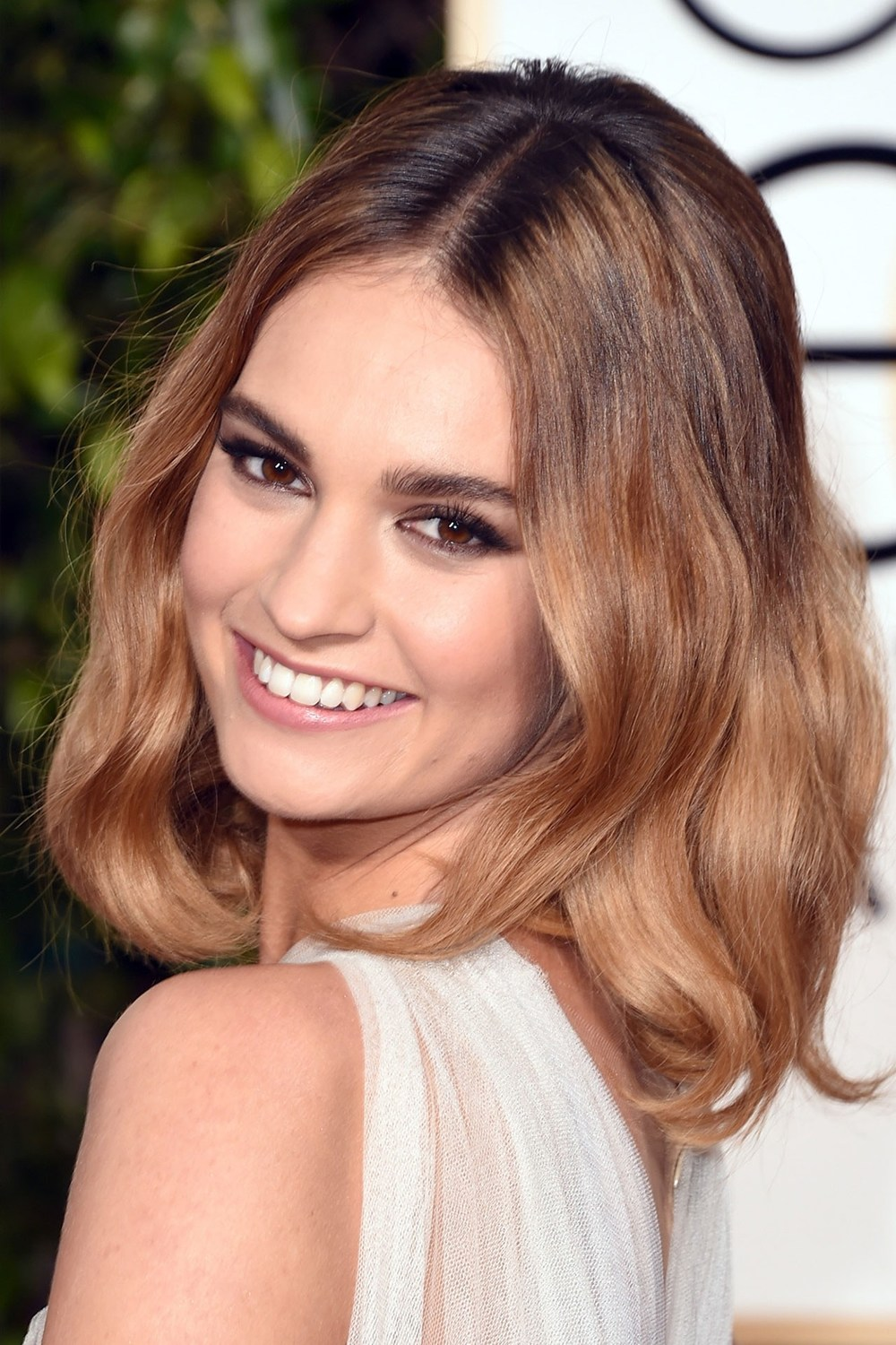 The lush Lily James wore her hair in tousled waves, offset by smoky eyes.