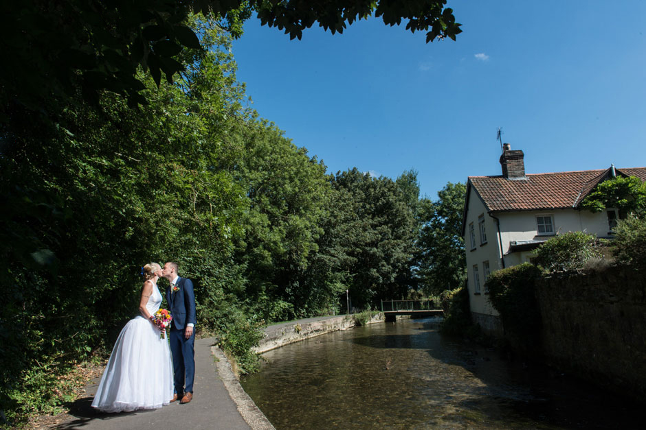 bride and groom by a stream in dorchester, dorset