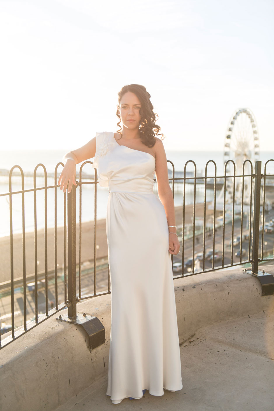 bride stands in winter wedding sunlight over looking brighton
