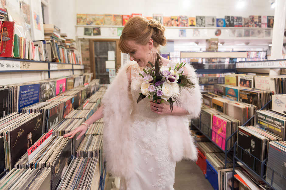 bride flicking though records in a shop in Rye