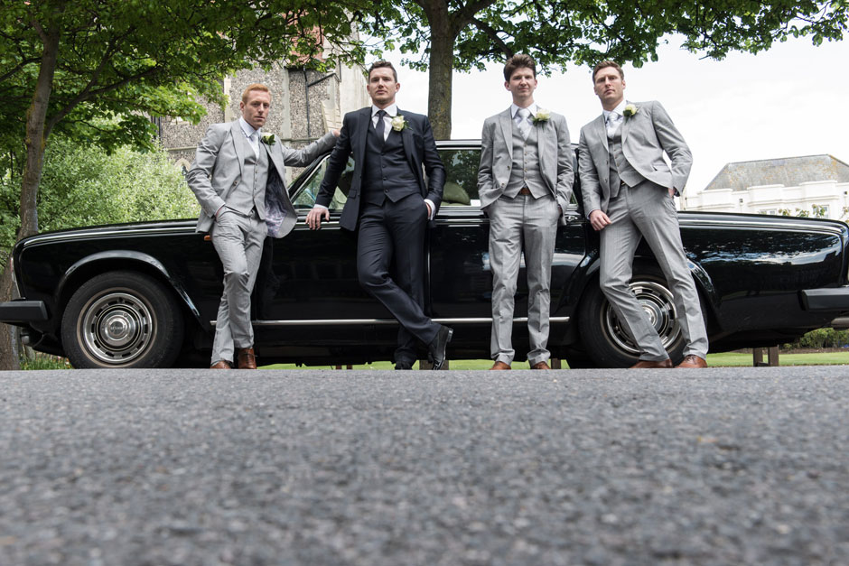 the groomsmen looking super cool against a rolls royce