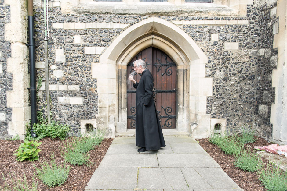 A vicar smoking a ciggy after a wedding ceremony