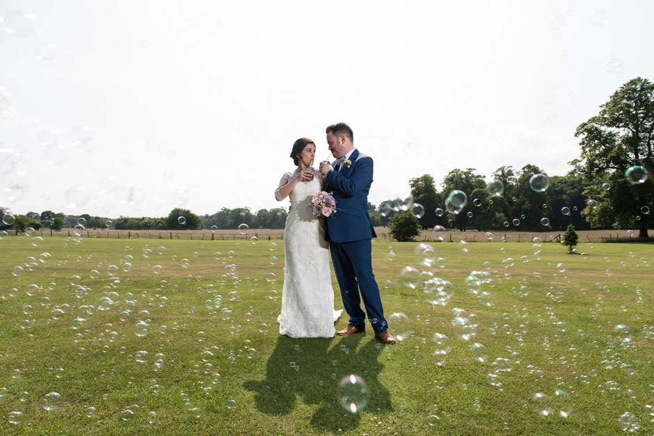 A bride and groom with lots of bubbles
