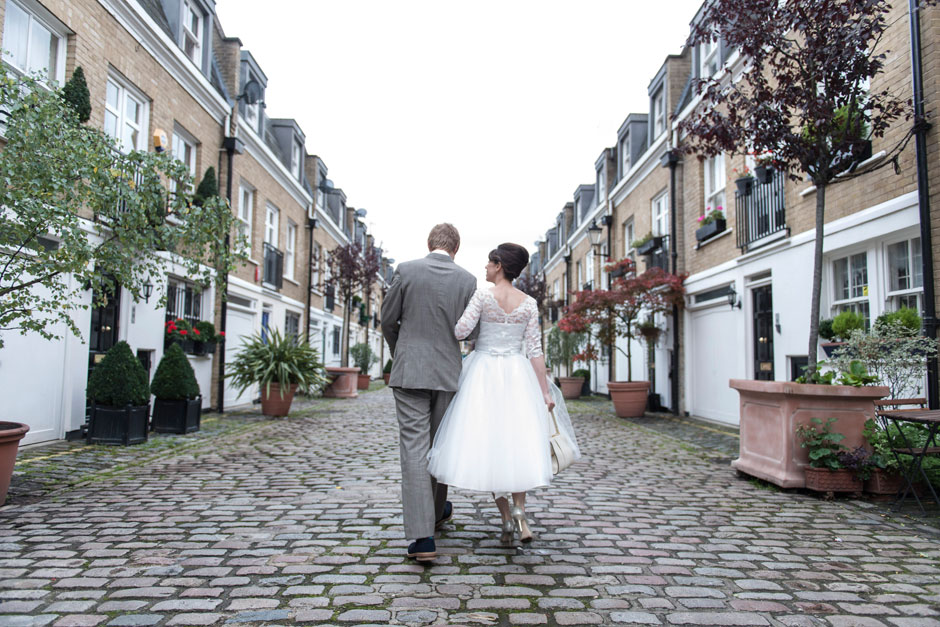 a mod wedding couple walk down a london muse