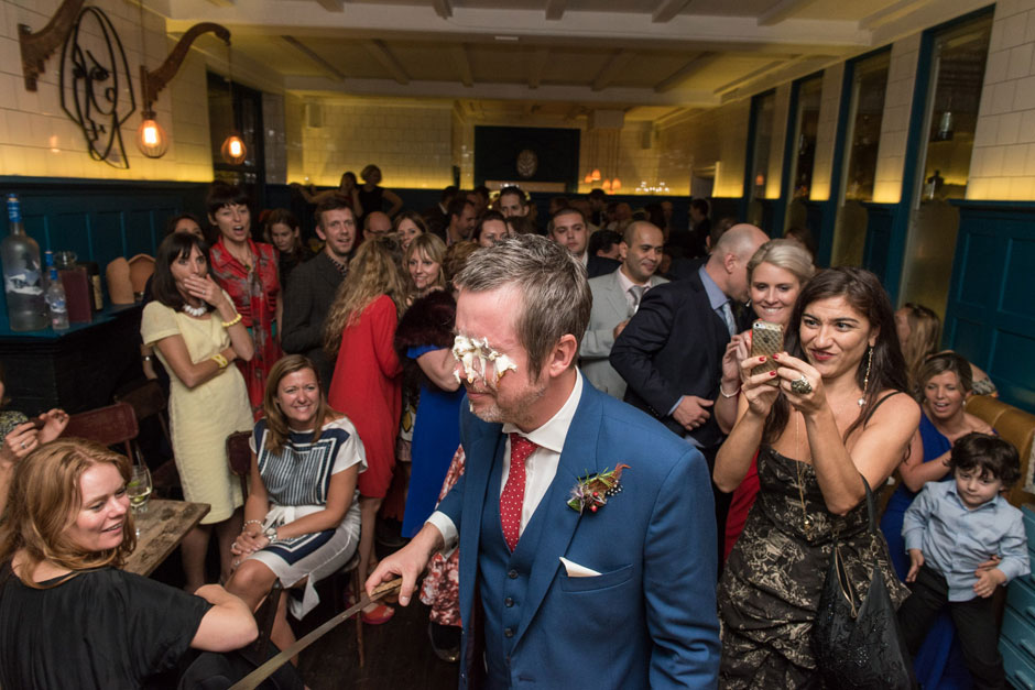 The groom has wedding cake thrown in his face by the bride