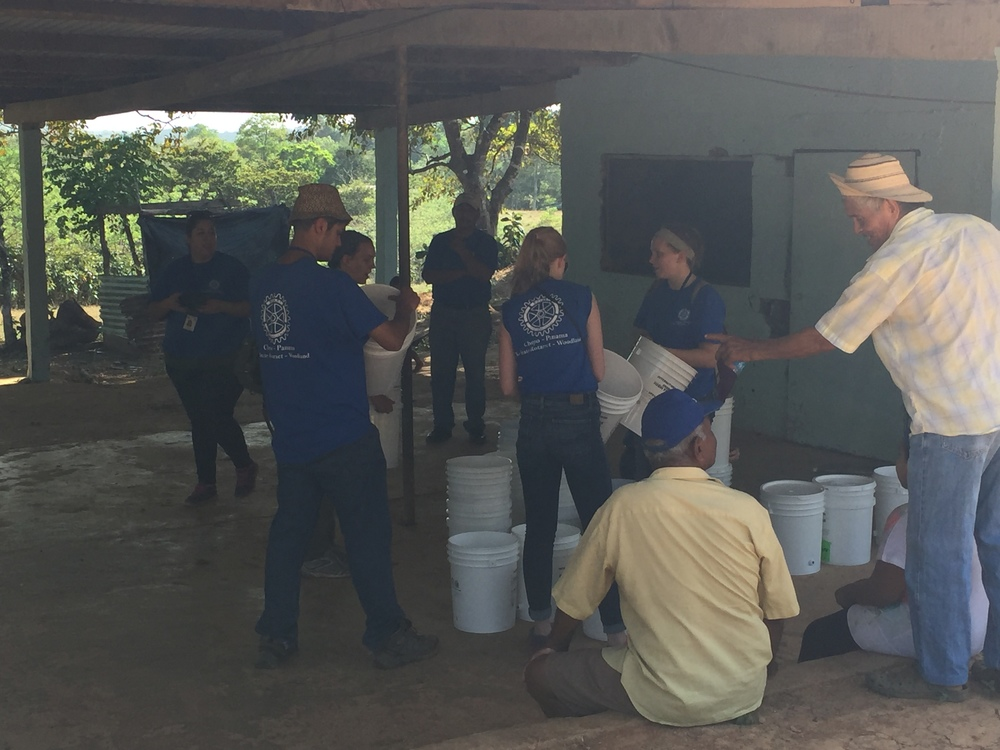 Assembling water filters while families gather to receive a filter and food.